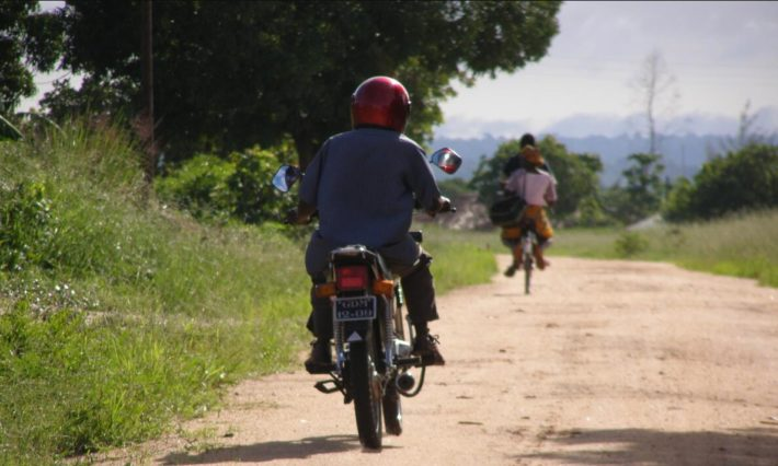 Bicycle and moped, on the sandy road, are transport for most people.